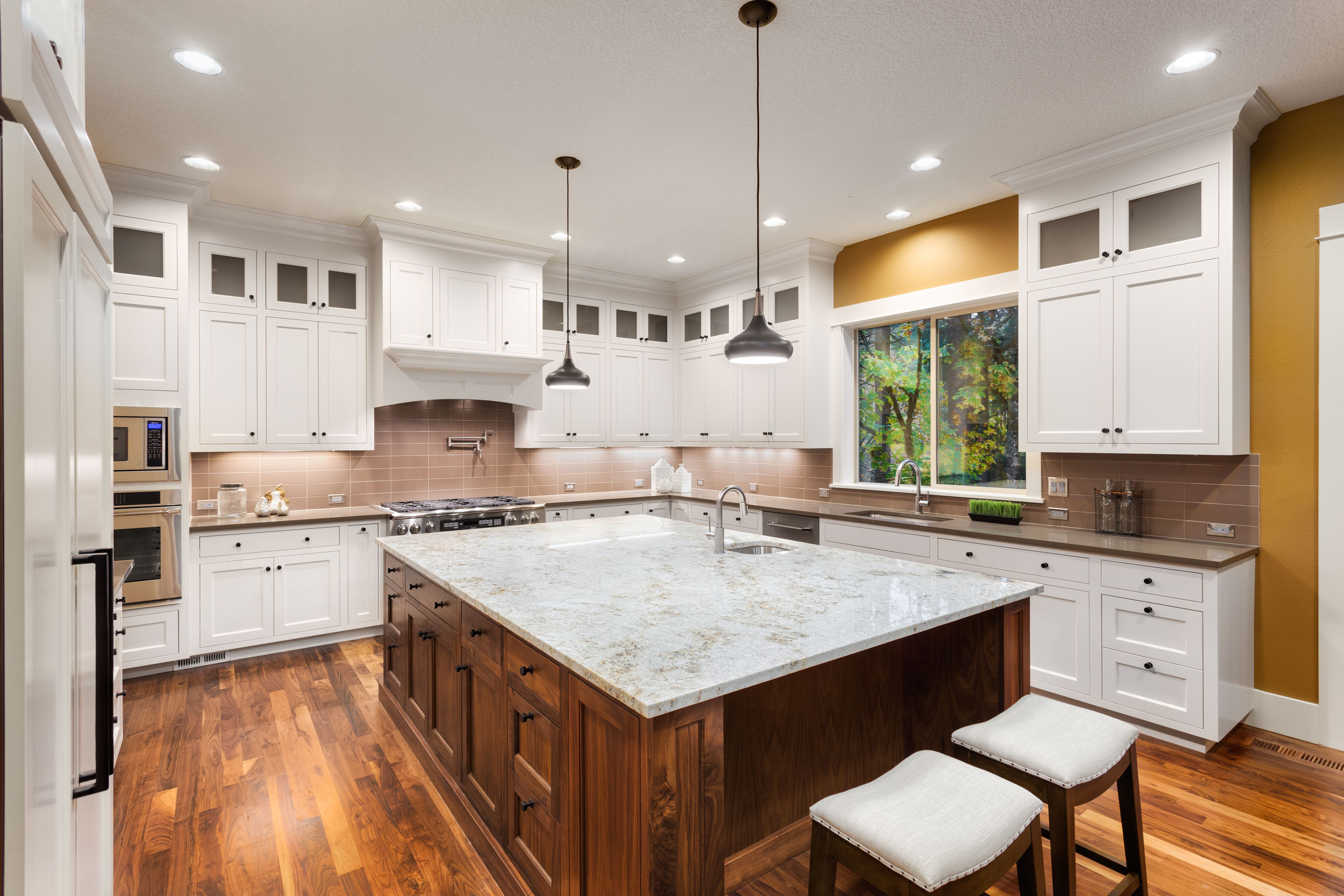 50834053 - large kitchen interior with island, sink, white cabinets, pendant lights, and hardwood floors in new luxury home